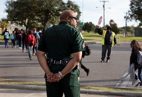 Image of police officer watching school children cross a parking lot