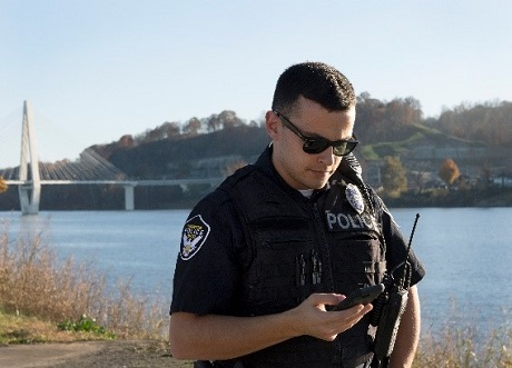 Image of police officer looking at his mobile phone